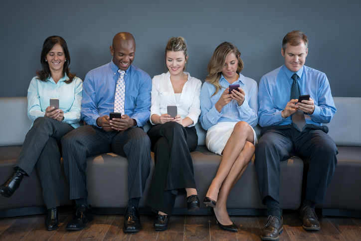 Group of business people social networking on their cell phones at the office